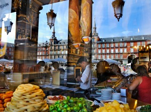 Plaza Mayor reflected in the window of a tapas bar displaying its food.